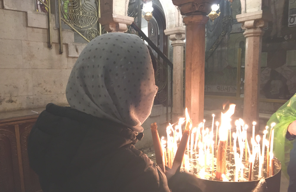 Mujer encendido velas en la iglesia del Santo Sepulcro